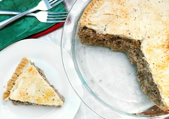 Slice of pork pie recipe or tourtiere recipe on white plate with fork