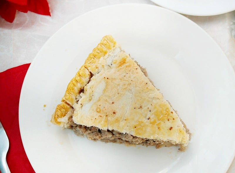A slice of tourtiere recipe on a white plate with red napkin