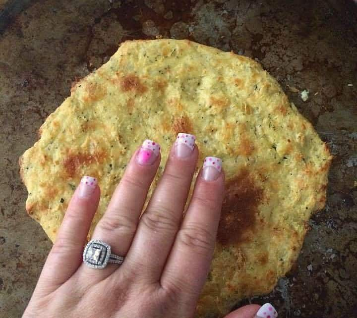 fathead pizza with hand over it to show size