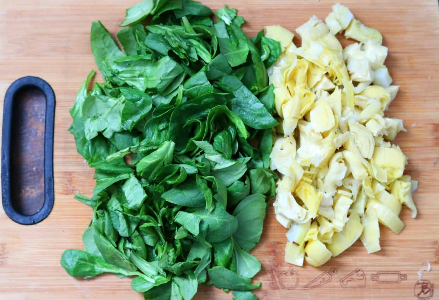 Chopped spinach and artichokes on a cutting board